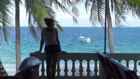 室外阳台的年轻女人有蓝色海风景和帆船的 在夏天大阳台和航行的女孩身分 股票视频