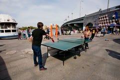 室外青少年的女孩和男孩戏剧的乒乓球 库存照片