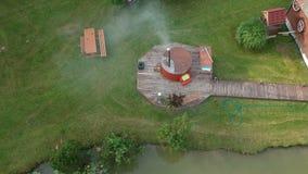 室外面汤木盆和池塘在木公共浴室附近,空中 股票录像