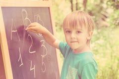 室外黑板实践的计数和的算术的逗人喜爱的小男孩 定调子 库存图片