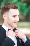 室外黑服装和purpure的弓领带的典雅的新郎 免版税库存图片