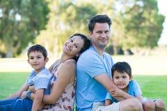 室外轻松的人种间家庭的公园 免版税库存照片
