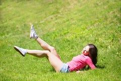 室外锻炼微笑的愉快的做的瑜伽的妇女 免版税图库摄影