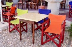 室外黄色,蓝色和橙色木的扶手椅子 免版税库存照片