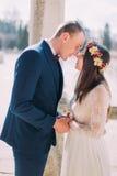 室外画象愉快肉欲婚礼夫妇拥抱 去美丽的年轻的新娘亲吻与英俊的新郎 免版税库存照片