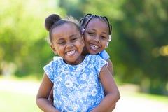 室外画象逗人喜爱的年轻黑人姐妹-非洲人民 库存图片
