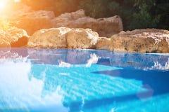 室外inground住宅游泳池在有浴盆的后院 太阳火光 免版税库存照片