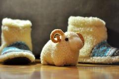 室拖鞋在地板上,并且玩具公羊在它旁边站立 免版税库存图片