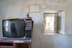 室毁坏与家具和老电视 免版税库存照片