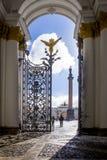 宫殿正方形、曲拱总参谋部和与一个天使的亚历山大大帝的专栏的看法通过一个开放的铸铁门, St 免版税库存照片