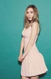 害怕女孩,站立在摆在绿色背景的一件短的桃红色礼服在演播室 定调子 图库摄影