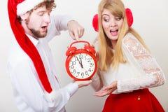 害怕的夫妇妇女和人有闹钟的 免版税库存图片