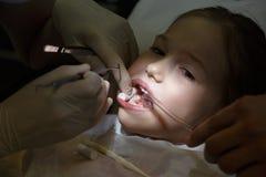 害怕的女孩在牙医办公室,在治疗期间的痛苦中 图库摄影
