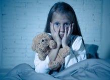 害怕的女孩覆盖物面孔用在恐惧的手在黑暗中在晚上 免版税库存图片