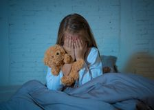 害怕的女孩覆盖物面孔用在恐惧的手在黑暗中在晚上 库存图片