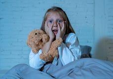 害怕的女孩覆盖物面孔用在恐惧的手在黑暗中在晚上 库存照片