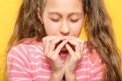 害怕的女孩闭上了眼睛报道嘴手重音 库存照片