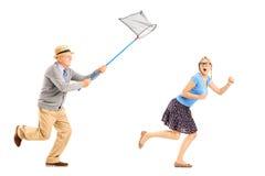 害怕的女性尝试对从人的逃亡有蝴蝶网的 免版税库存照片