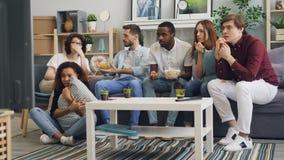 害怕的年轻人观看在电视的恐怖和在家吃快餐的学生 股票视频