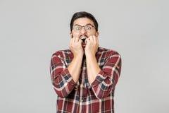 害怕的情感惊奇的男性模型被隔绝在灰色背景 库存照片