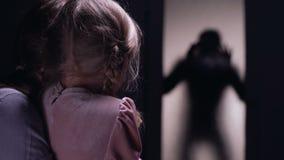 害怕的掩藏在屋子,犯罪剪影开门里的妇女和女儿 影视素材