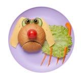 害怕的狗由面包和菜做成在板材 免版税图库摄影