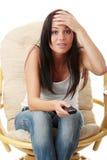 害怕的电视注意的妇女年轻人 免版税库存照片