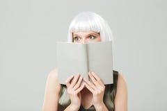 害怕的相当少妇用书盖了她的面孔 免版税库存图片