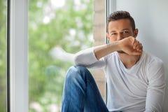害羞的人关闭面孔用手坐窗口基石 免版税库存照片