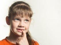 害羞的女孩画象有一个手指的在她的嘴,周道地查寻 免版税图库摄影