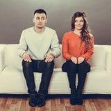 害羞的妇女和人坐沙发 第一个日期 免版税库存图片