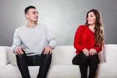 害羞的妇女和人坐沙发 第一个日期 库存图片