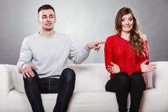 害羞的妇女和人坐沙发 第一个日期 免版税库存照片