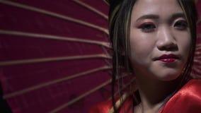 害羞的日本妇女看,当微笑和转动她的伞时 影视素材