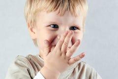 害羞的白肤金发的男孩皮他的鼻子和嘴用暗藏的手 库存照片