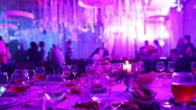 宴会桌在有玻璃和一个蜡烛的,一块玻璃一家餐馆用在宴会桌上的红色和白葡萄酒在a 股票录像