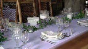 宴会装饰了桌,与利器 婚礼装饰在宴会大厅里 一张欢乐桌的服务,板材,餐巾 股票录像