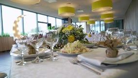 宴会装饰了桌,与利器 婚礼装饰在宴会大厅里 一张欢乐桌的服务,板材,餐巾 股票视频