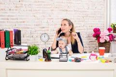 家业-远程办公女实业家,并且有孩子的母亲打一个电话 库存照片