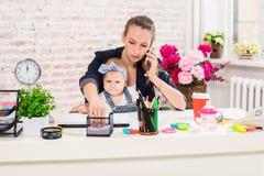 家业-远程办公女实业家,并且有孩子的母亲打一个电话 图库摄影