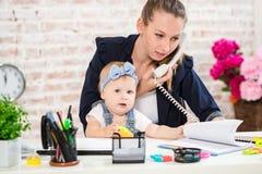 家业-远程办公女实业家,并且有孩子的母亲打一个电话 库存图片
