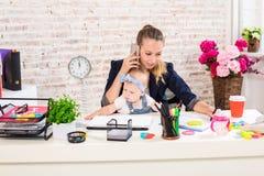 家业-远程办公女实业家,并且有孩子的母亲打一个电话 免版税库存照片
