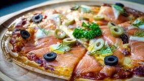 家做了与三文鱼和橄榄的薄饼 免版税库存照片