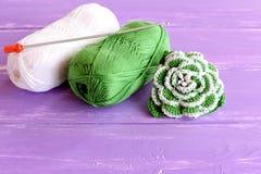家做了用小珠装饰的绿色和白色钩针编织花 棉纱品和钩针两个丝球  免版税图库摄影