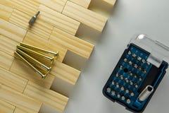 家具螺栓和螺丝起子比特设置有木块背景 库存图片