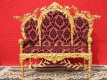 家具金黄ornated在红色沙发 免版税库存图片