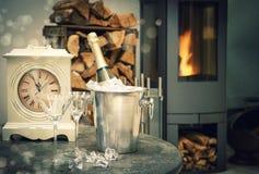 家内部用香槟、古色古香的时钟和壁炉 免版税图库摄影