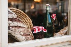 家制面包、一个瓶酒或其他饮料,一个瓶子在玻璃的果酱在咖啡馆或农舍 窗口装饰 库存图片