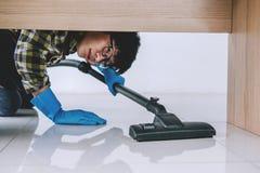 家务和家事清洁概念,蓝色橡胶手套的愉快的年轻人使用在地板上的吸尘器在家 库存照片