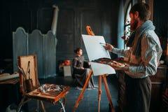 画家反对女性伪装者的图画画象 库存图片